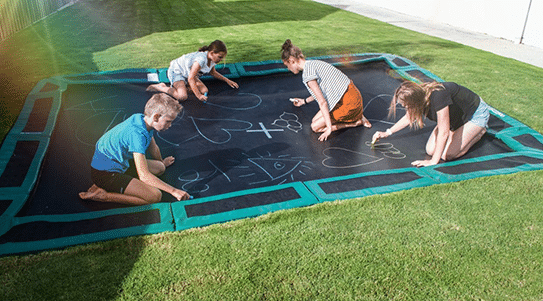 Kids playing on in-ground trampoline